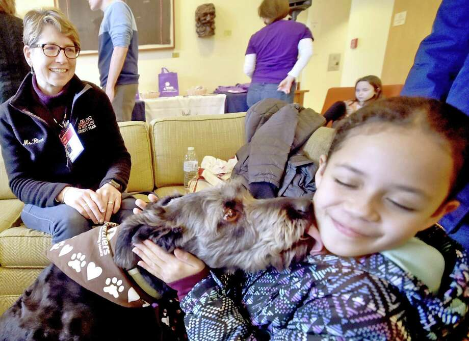 Leila Martinez, 8, of New Haven, right, gets a kiss from certified therapy dog Sophia, a rescued mixed-breed, on Saturday with her handler Roben River, of Woodbridge, representing dog training facility Paw's N' Effect of Hamden . Photo: Peter Hvizdak / Hearst Connecticut Media / New Haven Register