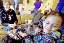 Leila Martinez, 8, of New Haven, right, gets a kiss from certified therapy dog Sophia, a rescued mixed-breed, on Saturday with her handler Roben River, of Woodbridge, representing dog training facility Paw's N' Effect of Hamden .