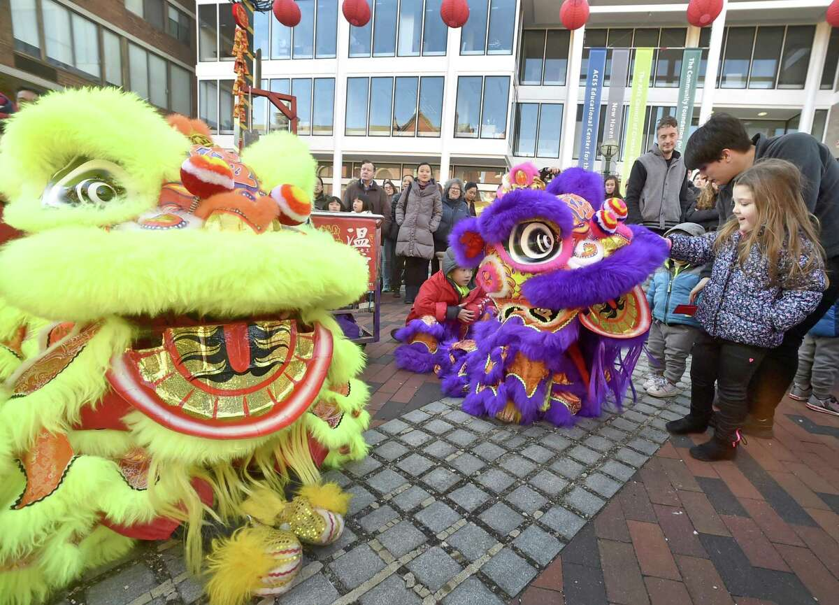 New Haven, Connecticut -Saturday, February 17, 2018: Emma Rioux, 4, of Meriden and her mother Randi Wilson of Meriden pet a dancing dog puppet at the Lunarfest 2018 Parade on Audubon Street during New Haven's 7th annual Lunar New Year festival Saturday sponsored by the Yale-China Association and other New Haven organizations celebrating the Chinese New Year and the Year of the Dog featuring the Lunarfest Parade and free events at Yale's Luce Hall, the New Haven Museum and other New Haven venues