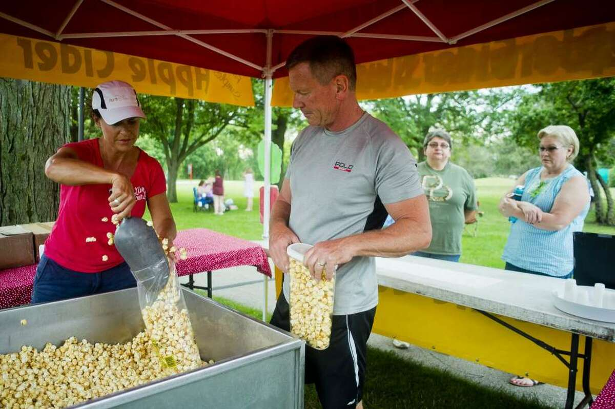 FILE:Katie Bugbee, left, and Tim Bugbee, center left, both of Clare, serve kettle corn while Jerilyn O'Connor of Midland, center right, and Karon Solberg of Midland, right, wait during Tunes by the Tridge on Thursday, June 22, 2017 in Chippewassee Park.
