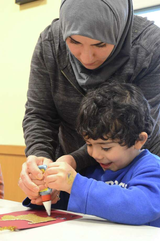 Alia Mahdi of Stamford helps her son, Musa, 3, at the Darien Library's Chinese New Year craft event on Friday, Feb. 16, 2018, in Darien, Conn. Photo: Jarret Liotta / For Hearst Connecticut Media / Darien News Freelance