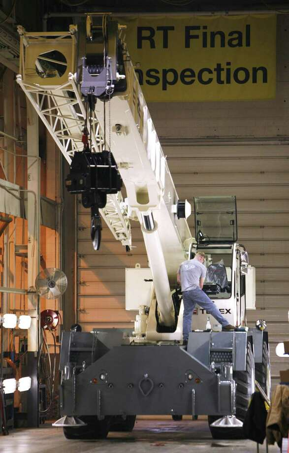 A worker inspects a crane in April 2008 at a Terex plant in Waverly, Iowa, which the company closed in 2016 amid a consolidation of U.S. plants. In 2017 for the first time in two years, Westport, Conn.-based Terex added to its U.S. workforce, with 5,000 workers as of December from 4,900 the year before. (AP Photo/Charlie Neibergall) Photo: Charlie Neibergall / AP / AP
