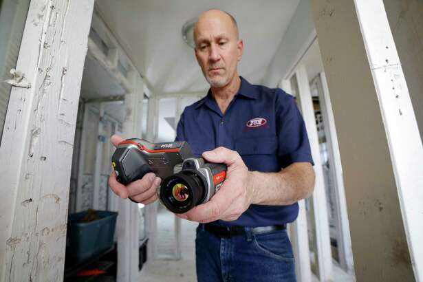 Gordon Fox, owner of Fox Inspection Group,  uses a thermal imaging camera to check for moisture inside the studs at a home in Meyerland, TX, Feb. 17, 2018. (Michael Wyke / For the  Chronicle)