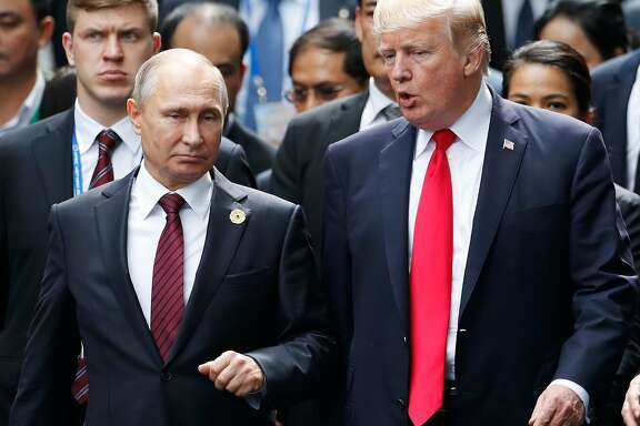 "(FILES) In this file photo taken on November 11, 2017 US President Donald Trump (R) and Russia's President Vladimir Putin talk as they make their way to take the ""family photo"" during the Asia-Pacific Economic Cooperation (APEC) leaders' summit in the central Vietnamese city of Danang. President Donald Trump, hitting out at the probes and congressional hearings into Russian election meddling, said on February 18, 2018 Moscow is succeeding beyond its ""wildest dreams"" if its intention is to sow discord within the United States.""They are laughing their asses off in Moscow. Get smart America!"" Trump said in an early morning tweet.It was one of a series of tweets posted by Trump in the wake of the indictments filed Friday by special counsel Robert Mueller against 13 Russians for meddling in the 2016 US presidential election.  / AFP PHOTO / POOL / JORGE SILVAJORGE SILVA/AFP/Getty Images"