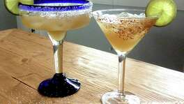 The classic margarita cocktail in the traditional margarita glass rimmed with kosher salt, left, and in a martini glass rimmed with lime chile salt.