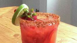 The Muddled Strawberry Margarita in a glass rimmed with lime chile salt.