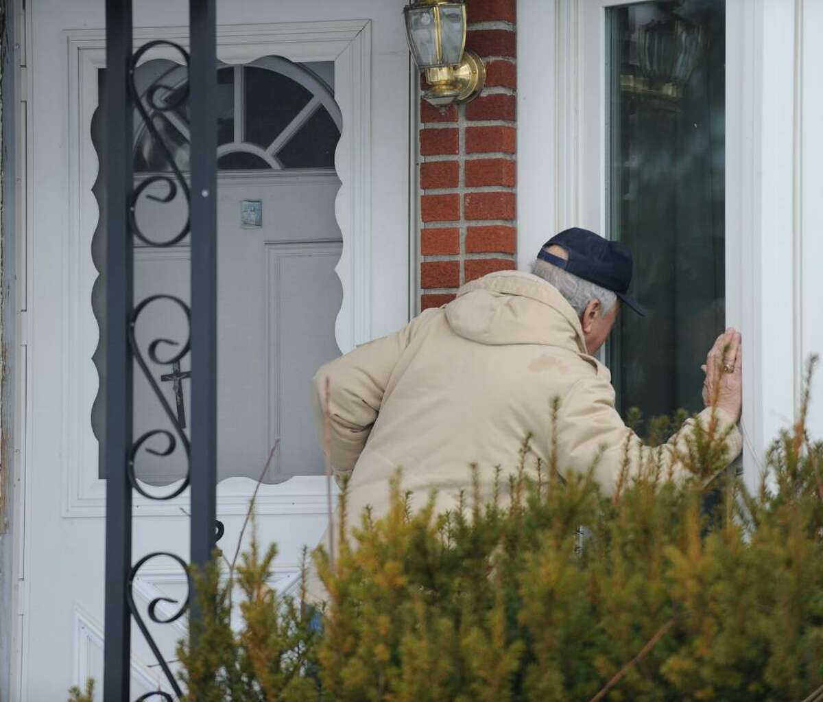 Jim Roti Roti looks in the window of 20 Industrial Park Road in Troy looking for his cousin Louis Pisaniello, 82, an Alzheimer's patient moments before the city marshal called for his eviction Dec. 10. (Skip Dickstein / Times Union)