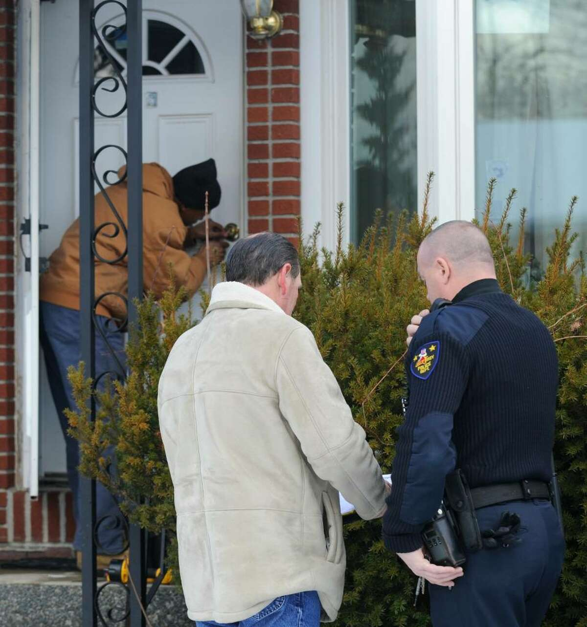 A locksmith removes the locks on 20 Industrial Park Road in Troy, New York in the presence of the City Marshall, Jack McCann(l, foreground) and a Troy Police officer, the home of Louis Pisaniello 82, an Alzheimers patient moments before the City Marshall called for his eviction December 10, 2009. (Skip Dickstein / Times Union)