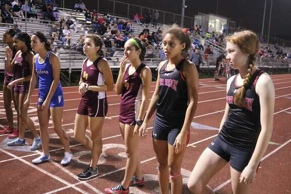 A pair of Lady Deer stand at the starting line, waiting for the start to a race at the Brown Relays last Friday night.