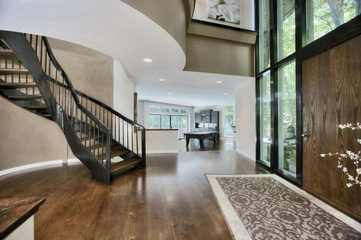 The spacious two-story foyer has a floating staircase to the second floor.