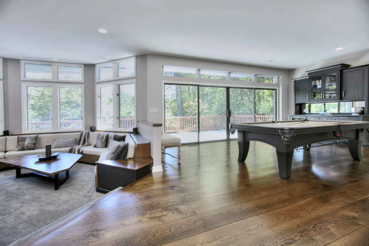 The cavernous living room features a sunken area with built-in seating around a floor-to-ceiling stone fireplace and a game room area with a bar service area. French doors lead to the long wood deck.