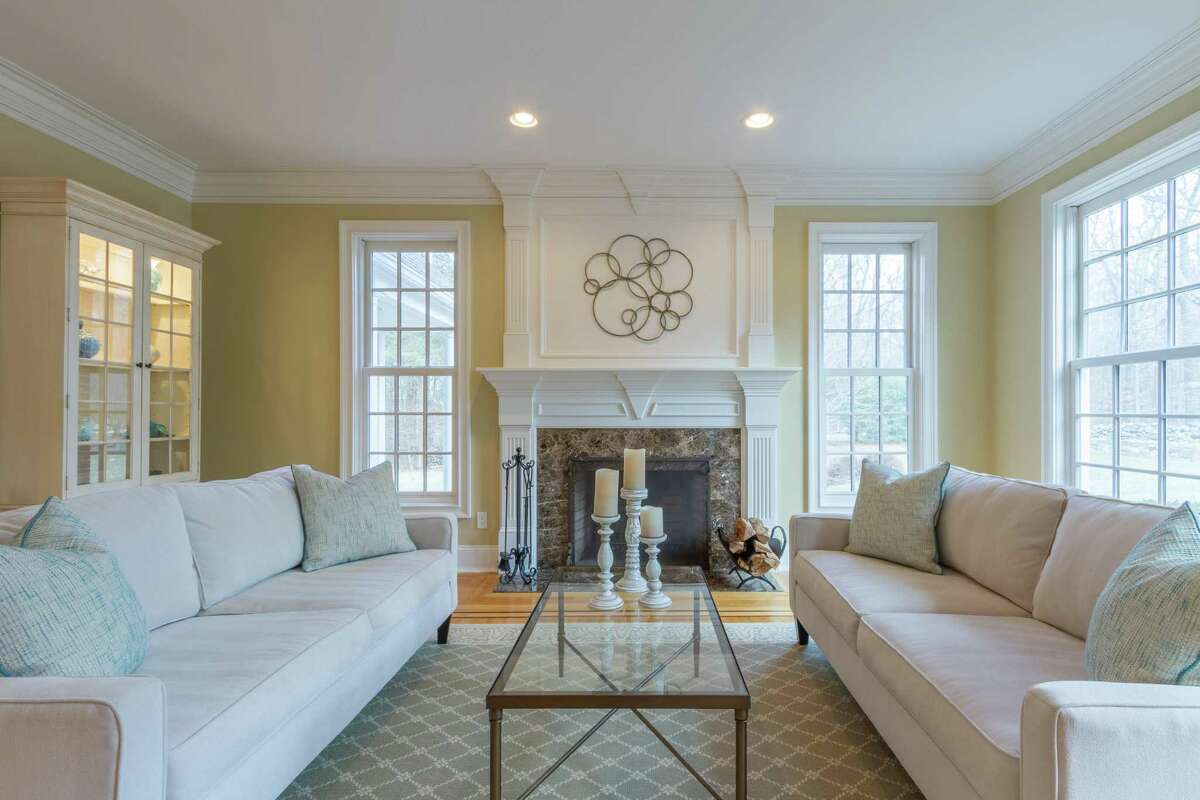 The formal living room has a marble fireplace and elegant crown molding and millwork, which is found throughout the house, including on the finished third floor.