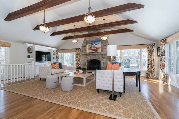 The family room features a cathedral ceiling with exposed beams and a floor-to-ceiling stone fireplace.