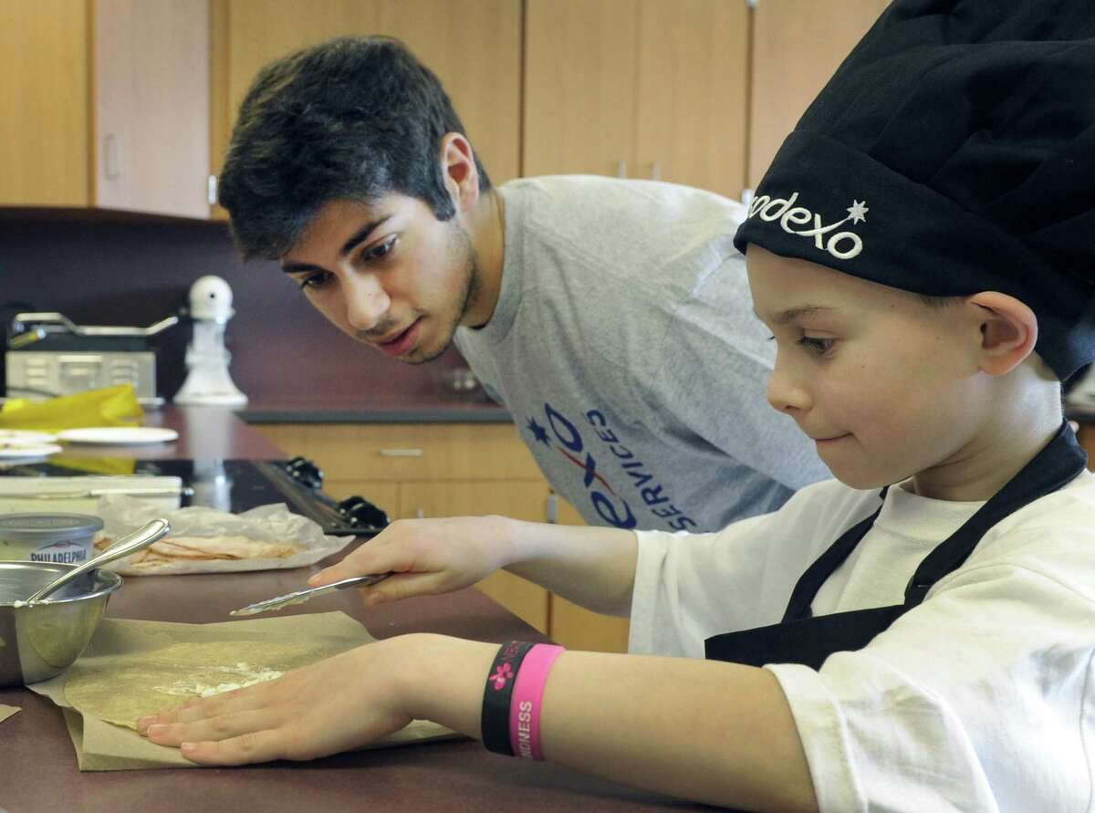 """Luke Cassavechia, 7, a first-grader at Rockewell School, makes his """"The Awesome Sandwich"""" under the watchful eye of Joe Marji, 18, a Bethel High School senior. The two were competing in the Future Chefs competition at Bethel High School in Bethel Conn., Friday, March 7, 2014."""