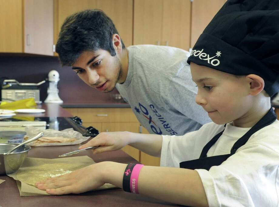 "Luke Cassavechia, 7, a first-grader at Rockewell School, makes his ""The Awesome Sandwich"" under the watchful eye of Joe Marji, 18, a Bethel High School senior. The two were competing in the Future Chefs competition at Bethel High School in Bethel Conn., Friday, March 7, 2014. Photo: Carol Kaliff / Carol Kaliff / The News-Times"