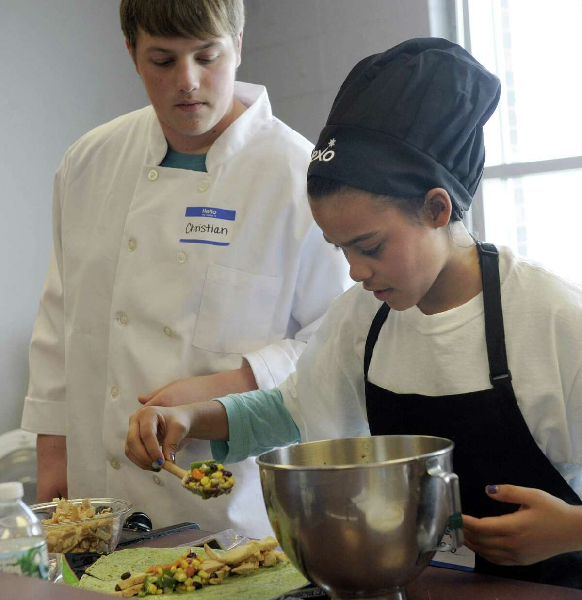 Christian Denninger, 17, left, a senior at Bethel High School is sous chef to Tessa Barrows, 11, from Johnson School, during the Future Chefs competition held at Bethel High School Friday, March 7, 2014. Tessa was the contest winner with her bean, salsa and chicken wrap.
