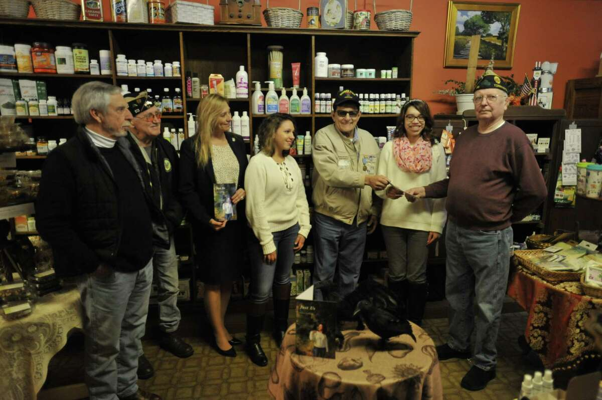 Torrington veteran Mike Galitello donated proceeds from his third book to aid city veterans Friday, with plans to write more in the future. From left: Rob Carr, American Legion Post 38 Commander Bruce Falls, State Rep. Michelle Cook, D-Torrington, Isabella Pinto, Galitello, Olivia Pinto,Torrington Veterans Service Office manager Bud Atwood, and Pam Pinto.