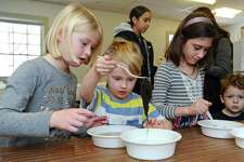 From left, siblings Emilia Londrigan, 7, Henry Londrigan, 5, and Darya Siman clean sheeps wool in a bowl of water before attempting to make it into a string of yarn during the winter break out day at Stamford Museum & Nature Center on Scofieldtown Road in Stamford, Conn. on Monday, Feb. 19, 2018.