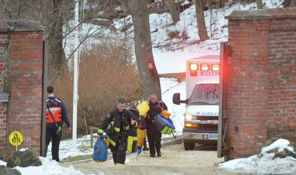 Emergency personnel including Westport Firfighters carry rescue equipment up a drive from a Stoney Point residence after a person was pulled from the Saugatuck River after jumping from the I-95 bridge on Monday February 19, 2018 in Westport Conn.