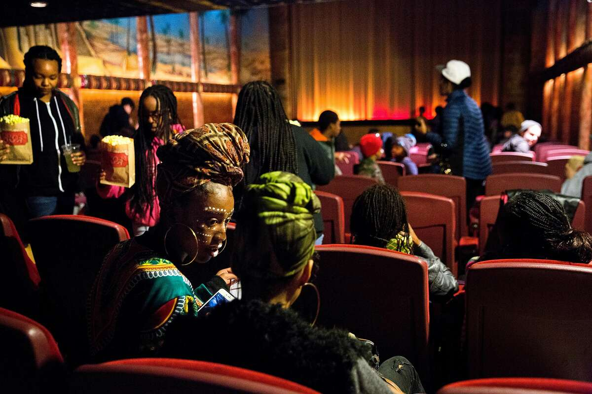 Amela Abrams, 15, and Nakeyla Davis, 15, of Youth Radio chat in their seats before a screening of Black Panther at the Grand Lake Theater Monday, Feb. 19, 2018, in Oakland, Calif.