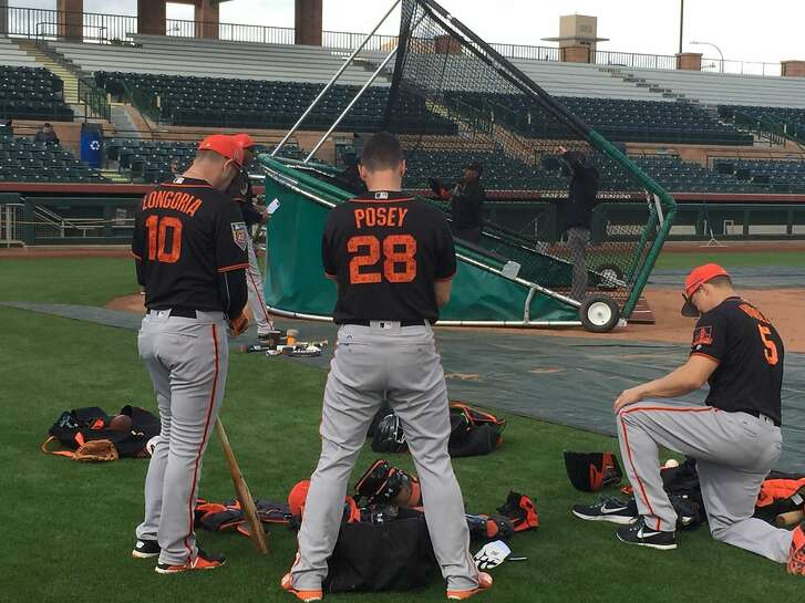 Evan Longoria, left, and Nick Hundley prepare to join Buster Posey for batting practice during the Giants' first full-squad workout of spring training Monday.