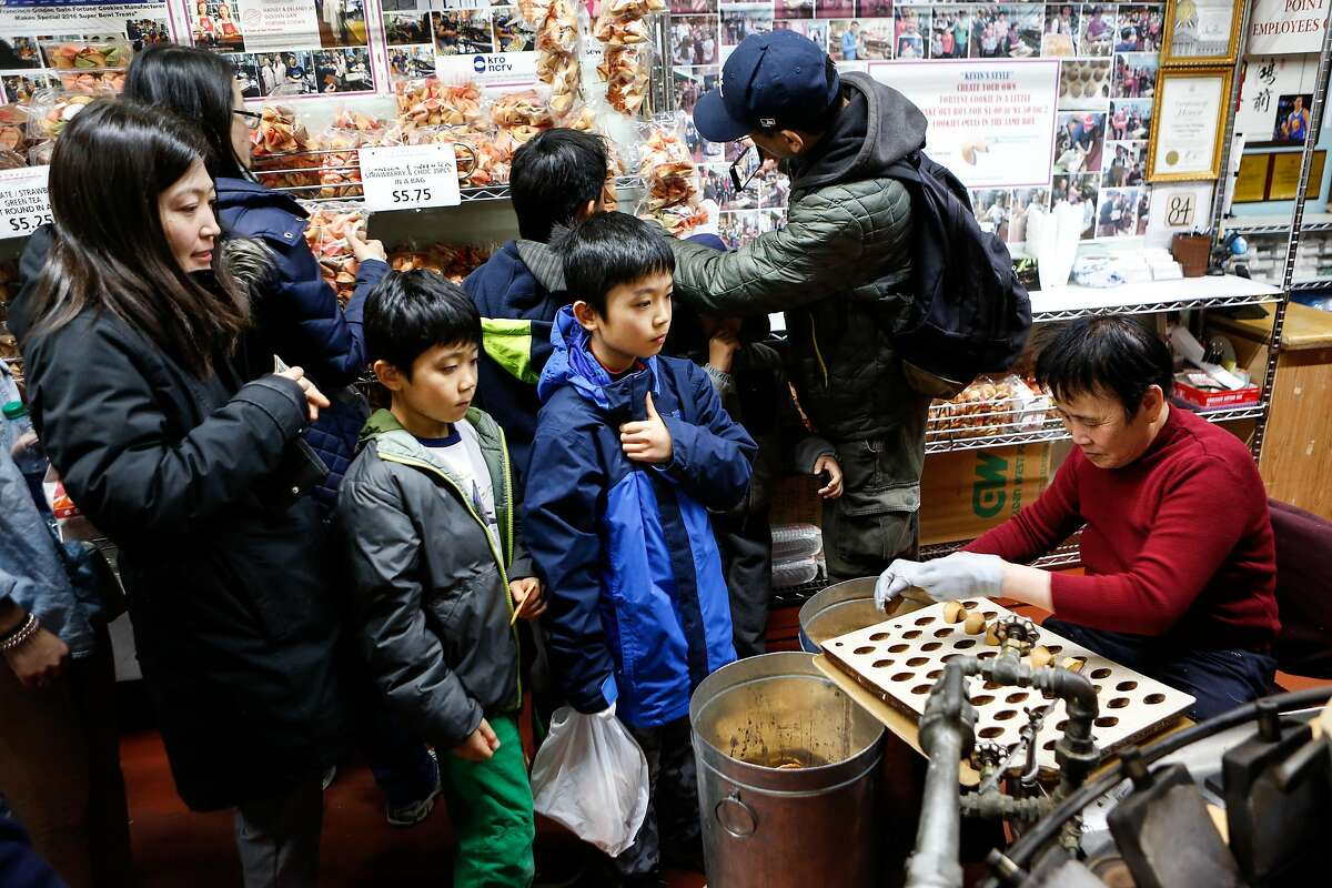 City Walks participants (L to R) Grace Tan and her sons Elliot, 7, and Caden, 9, sample fortune cookies at the last remaining hand rolled fortune cookie maker in Chinatown on Monday, February 19, 2018 in San Francisco, California.
