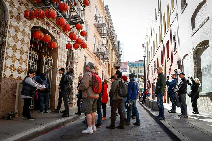 City Walks participants enter the last remaining temple in Beckett Alley during a tour through Chinatown on Monday, February 19, 2018 in San Francisco, California.