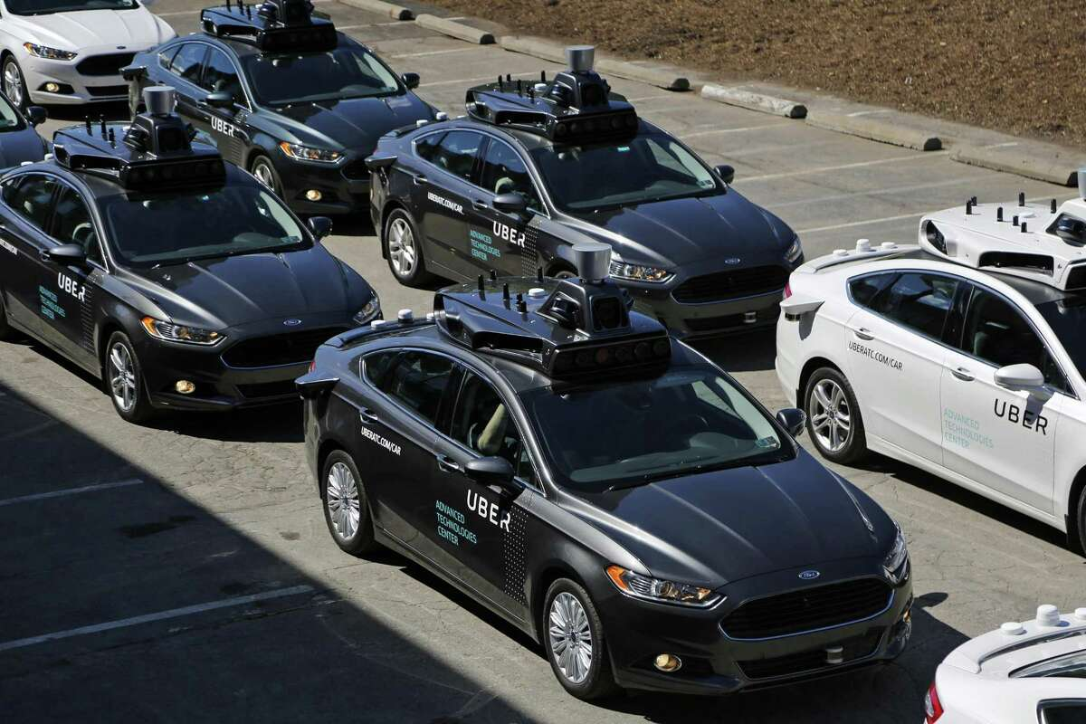 FILE- This Sept. 12, 2016, file photo, shows group of self driving Uber vehicles position themselves to take journalists on rides during a media preview at Uber's Advanced Technologies Center in Pittsburgh. Uber is testing the cars on the streets of Austin. (AP Photo/Gene J. Puskar, File)