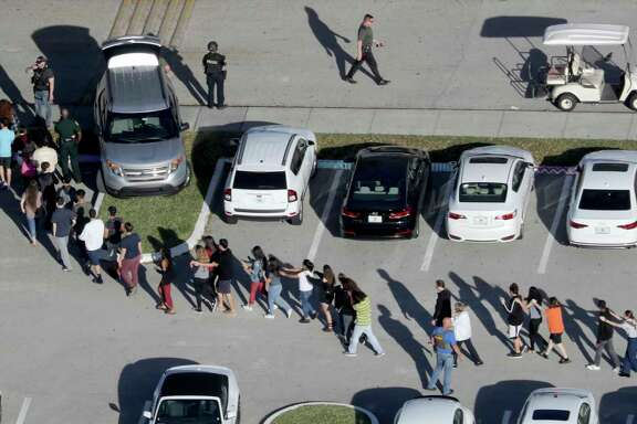 Students are evacuated by police from Marjory Stoneman Douglas High School in Parkland, Fla., after a shooter opened fire on the campus. (Mike Stocker/South Florida Sun-Sentinel)