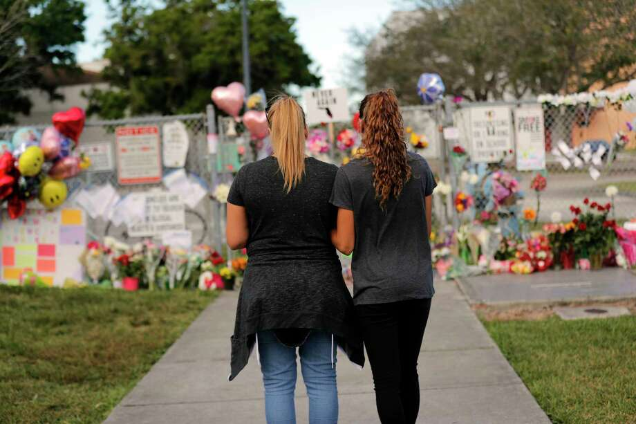 Sara Smith, left, and her daughter Karina Smith visit a makeshift memorial outside the Marjory Stoneman Douglas High School, where 17 students and faculty were killed in a mass shooting on Wednesday, in Parkland, Fla., Monday, Feb. 19, 2018. Nikolas Cruz, a former student, was charged with 17 counts of premeditated murder on Thursday. (AP Photo/Gerald Herbert) Photo: Gerald Herbert, STF / Copyright 2018 The Associated Press. All rights reserved.