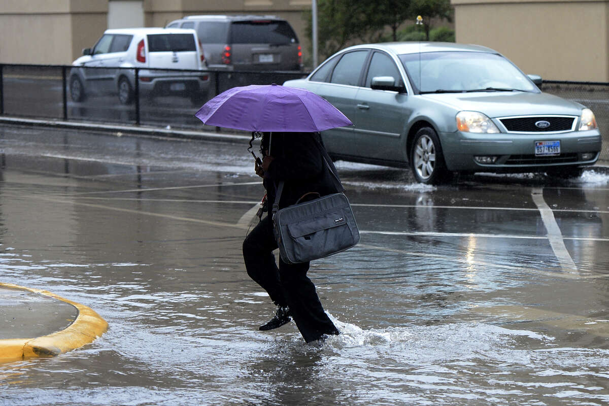 A pedestrian walks through a puddle while crossing Illinois Avenue in front of Midland Memorial Hospital in September of last year.