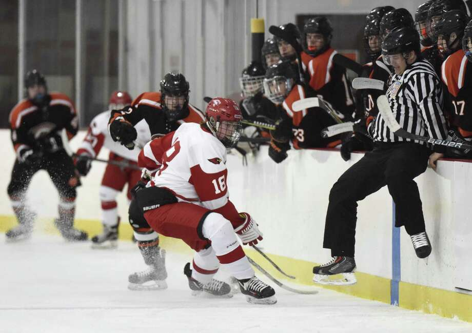 Greenwich's Connor Santry (18) and Ridgefield's Nick Cullinan (2) scramble for the puck as a referee jumps to avoid contact in Greenwich's 5-3 win over Ridgefield in the high school boys hockey game at Dorothy Hamill Skating Rink in Greenwich, Conn. Monday, Feb. 19, 2018. Photo: Tyler Sizemore / Hearst Connecticut Media / Greenwich Time