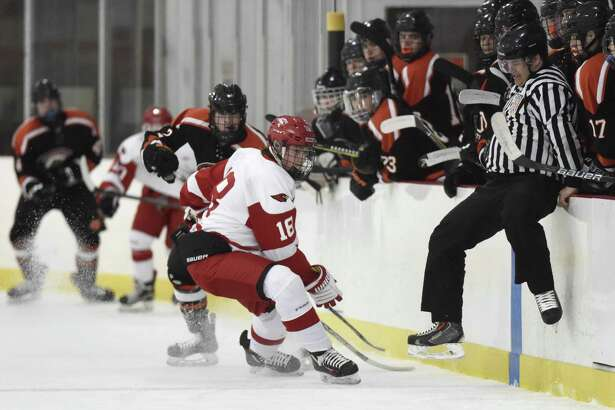Greenwich's Connor Santry (18) and Ridgefield's Nick Cullinan (2) scramble for the puck as a referee jumps to avoid contact in Greenwich's 5-3 win over Ridgefield in the high school boys hockey game at Dorothy Hamill Skating Rink in Greenwich, Conn. Monday, Feb. 19, 2018.