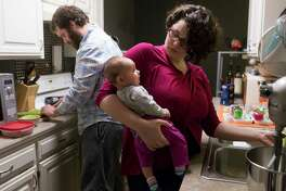 Laura Cameron holds 3-month-old Fiona as she and her husband, Keith, fix dinner in their Fayetteville, Ark., home.