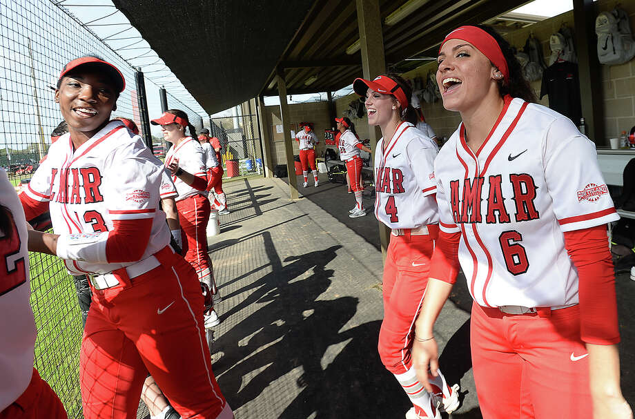 Lamar's (from right) Elizabeth Castillo, Savana Guidry, and Kimberly Mattox join teammates in cheering from the dugout as they take on the Washington Huskies in the first of Monday's home opening doubleheader games. Photo taken Monday, February 19, 2018 Kim Brent/The Enterprise Photo: Kim Brent, Beaumont Enterprise / BEN