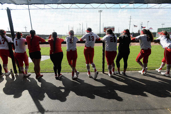 Lamar's Lady Cardinals line the dugout to cheer as they take on the Washington Huskies in the first of Monday's home opening doubleheader games. Photo taken Monday, February 19, 2018 Kim Brent/The Enterprise