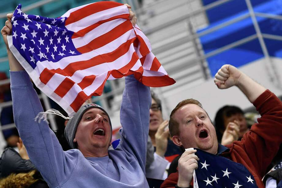 US fans cheer during the women's ice hockey semifinal game between the United States and Finland during the Pyeongchang 2018 Winter Olympic Games at the Gangneung Hockey Centre in Gangneung on February 19, 2018. / AFP PHOTO / Brendan SmialowskiBRENDAN SMIALOWSKI/AFP/Getty Images Photo: BRENDAN SMIALOWSKI / AFP