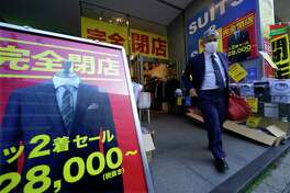 A man leaves a tailor in Tokyo's Nihombashi shopping and business district, Monday, Feb. 19, 2018. Japan has reported a trade deficit for January, its first in eight months, mainly due to seasonal factors. (AP Photo/Shizuo Kambayashi)