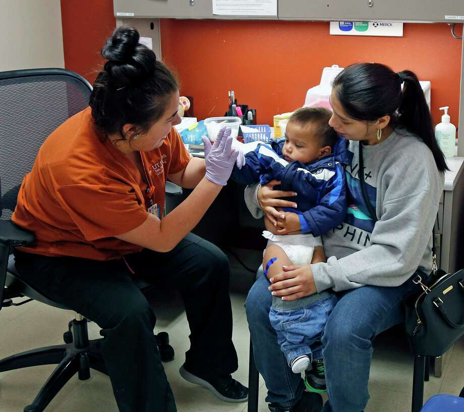 Caitlin Garcia, a student at the UT-San Antonio School of Nursing, gives a high-five to Alexander Almanza, 2, after administering his flu shot while he was held by his mom, April. It's not too late to get inoculated this season, officials say. Photo: Ronald Cortes, For The San Antonio Express News / 2017 Ronald Cortes