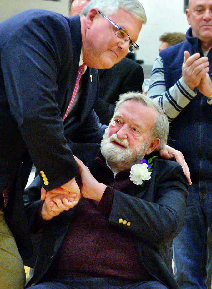 Former CCHS coach Don Bassett ,seated, is embraced by CCHS alum and former major league baseball player Gary Holle, who credited his sports successes to coach Bassett, during a ceremony naming the school's basketball court after Bassett Friday Feb. 9, 2018 in Troy, NY. At right is   (John Carl D'Annibale/Times Union) Photo: John Carl D'Annibale / 20042888A
