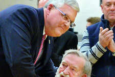 Former CCHS coach Don Bassett ,seated, is embraced by CCHS alum and former major league baseball player Gary Holle, who credited his sports successes to coach Bassett, during a ceremony naming the school's basketball court after Bassett Friday Feb. 9, 2018 in Troy, NY. At right is   (John Carl D'Annibale/Times Union)