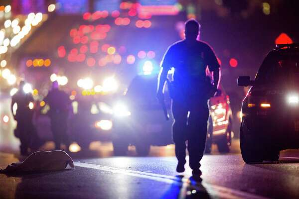 Houston Police officers investigate the scene where a woman was fatally struck by a vehicle on the southbound lanes of Gulf Freeway near Telephone Road Tuesday, Feb. 20, 2018.