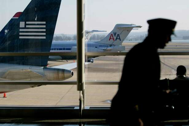 A pilot passes US Airways and American Airlines airplanes on the tarmac at Reagan National Airport in Washington, D.C., on Feb. 14, 2013. (