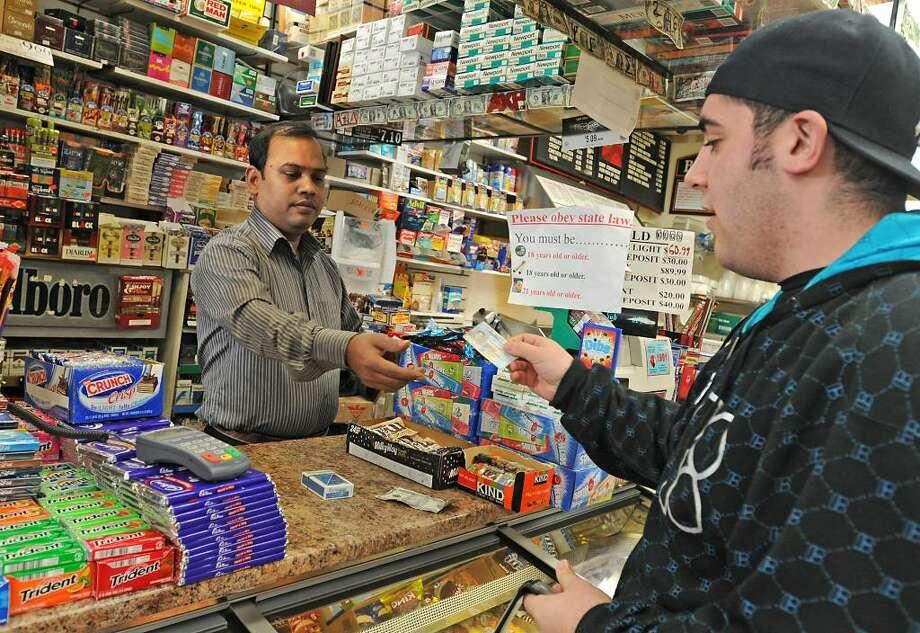 Ashif Mashud checks the ID of Marco Scalia at Easha Convenience store.  (Lori Van Buren / Times Union) Photo: LORI VAN BUREN