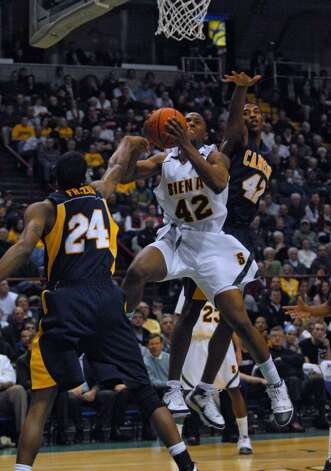 Siena's Alex Franklin drives to the basket while Canisius Elton Frazier, left, and Tomas Vazquez-Simmons, right, defend during Siena's 82-70 win over Canisius at the Times Union Center in Albany Monday night January 11, 2010. (Philip Kamrass / Times Union) Photo: PHILIP KAMRASS / 00006713A