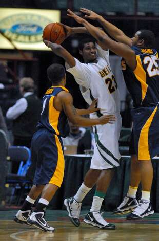 Siena's Edwin Ubiles, center, is defended by Canisius Frank Turner, left, and Rishawn Johnson, right, defend during Siena's 82-70 win over Canisius at the Times Union Center in Albany Monday night January 11, 2010. (Philip Kamrass / Times Union) Photo: PHILIP KAMRASS / 00006713A
