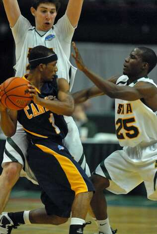 Canisius Frank Turner is defended by Siena's Ryan Rossiter, left, and Ronald Moore during Siena's 82-70 win over Canisius at the Times Union Center in Albany Monday night January 11, 2010. (Philip Kamrass / Times Union) Photo: PHILIP KAMRASS / 00006713A