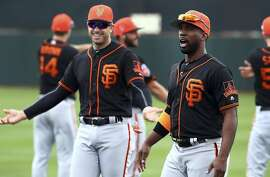 San Francisco Giants' Andrew McCutchen, right, and Evan Longoria during a spring training baseball practice on Monday, Feb. 19, 2018 in Scottsdale, Ariz. (AP Photo/Ben Margot)
