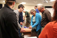 Stop the Bleed participant Deb Heidemann (center) practices packing a wound on a wound simulator at Monday's Stop the Bleed class, hosted by the Edwardsville Fire Department.