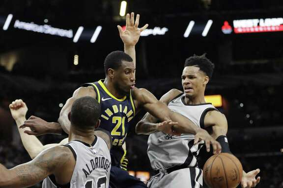 Indiana Pacers forward Thaddeus Young (21) blocks San Antonio Spurs guard Dejounte Murray, right, who was driving to the basket during the second half of an NBA basketball game, Sunday, Jan. 21, 2018, in San Antonio. (AP Photo/Eric Gay)